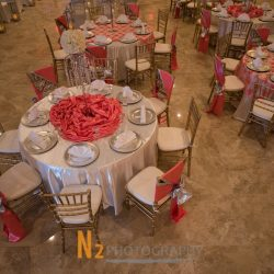View of tables with red centerpieces at our reception hall - Alegria Gardens