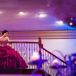 Girl in quinceanera dress on stairs at our party hall - Alegria Gardens