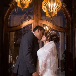 Couple kissing below lights at our wedding venue - Alegria Gardens