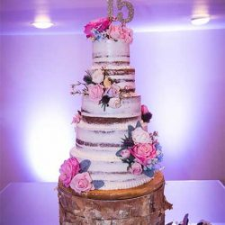 Layered wedding cake with pink flowers at our reception hall - Alegria Gardens
