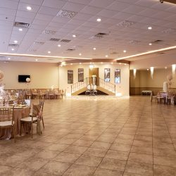 A photograph of the spacious dining hall at Alegria Gardens Reception Hall at Stacy in Houston featuring decorated tables and chairs.