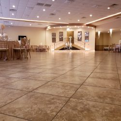 A picture of decorated tables and chairs inside of the dining hall at Alegria Gardens Reception Hall at Stacy in Houston.