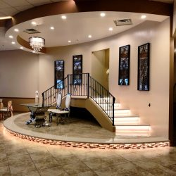 A picture of a table, two chairs, and a staircase at Alegria Gardens Reception Hall at Stacy in Houston.
