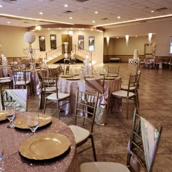 A close-up shot of decorated tables and chairs inside of the dining hall at Alegria Gardens Reception Hall at Stacy in Houston.