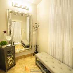 A picture taken inside of the changing room at Alegria Gardens at 529 in Houston featuring a large mirror, bright lights, and a soft bench.