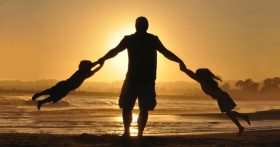 A father and a pair of children are on a beach at sunset, he's swinging both children by the arms.