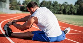 Man stretching on a track field