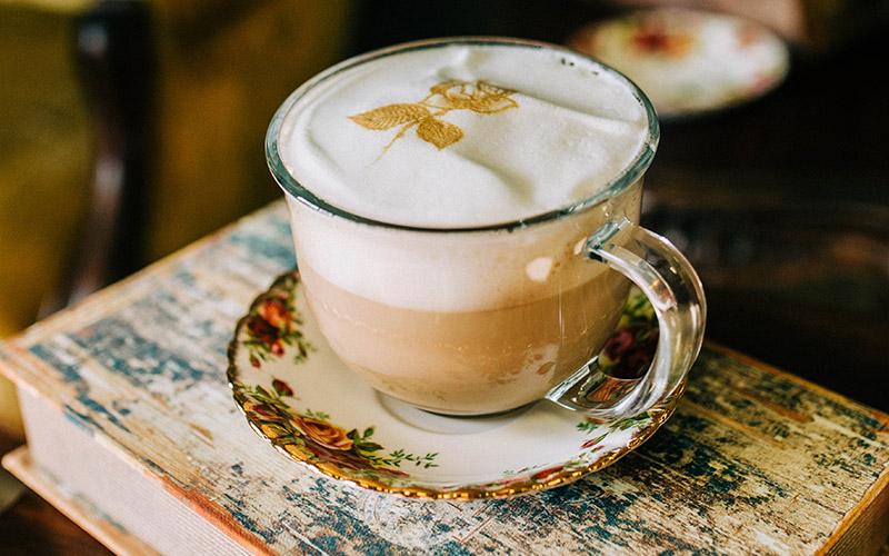 Coffee in glass mug with rose designed on foam