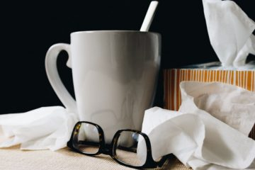 Getting sick with the flu. Using tissues and staying hydrated to combat the virus.