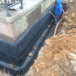 Worker in Trench With New Foundation Waterproofing Barrier