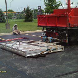A sealcoating job and asphalt repair job underway in Bridgeview