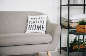 "Comfortable couch with pillow that reads, ""There is no place like home."""