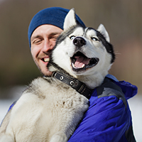 Husky dog close to a man in a blue jacket and cap - Animal Eye Associates