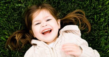 A young girl laughs and lays in the grass