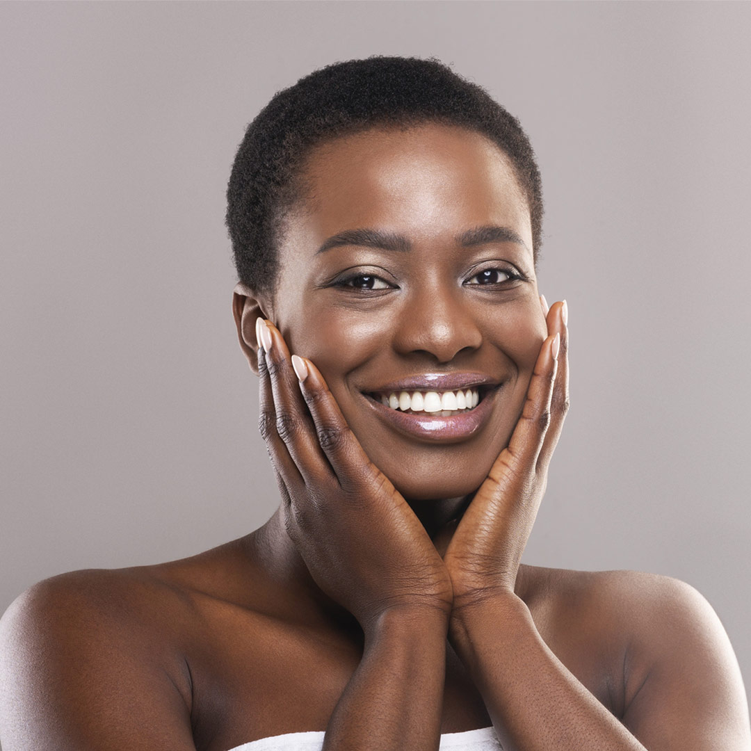 Beautiful afro woman with short hair touching face with perfect smooth skin
