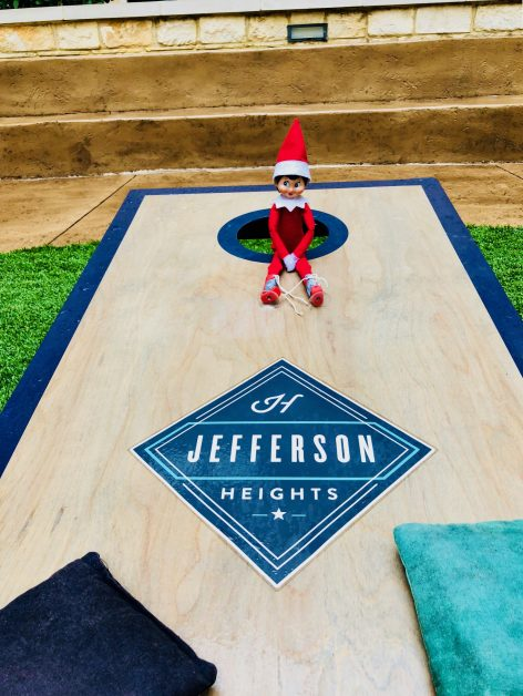 Sitting on the cornhole game in the courtyard at Jefferson Heights apartment