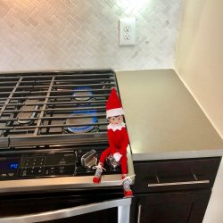 Elf on the shelf hanging out by the gas stoves at Alexan 5151
