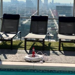 Elf on the shelf sitting in a lifesaver beyond the swimming pool at Skyhouse Main Downtown luxury apartments