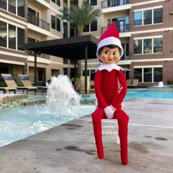 Elf on the shelf sitting in front of the pool at Alexan 5151 luxury apartments in Houston