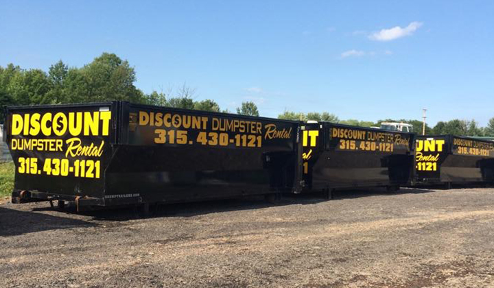 A line of black rental dumpsters with yellow lettering.