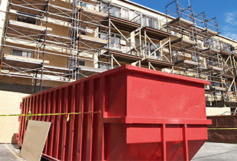 An image of a roll away red dumpster at the foot of a construction site for a tall building.