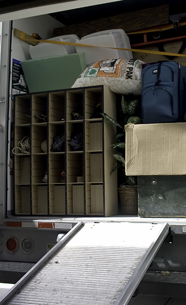 An image of a truck loaded with moving boxes and furniture.