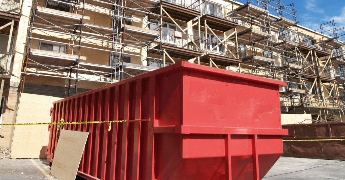 A red roll away dumpster at the base of an apartment building.