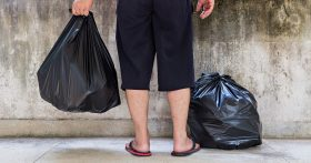 A person standing in front of concrete with several black trash bags.