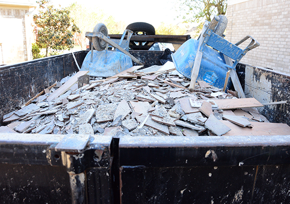 A dumpster is filled with old building materials and wheel barrels