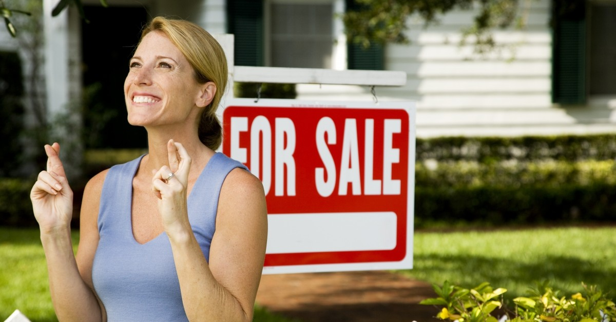 A woman stands, fingers-crossed in front of a for sale sign in a yard.