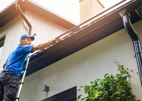 A man cleans gutters out.