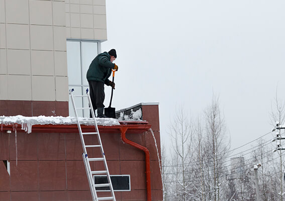 A person shovels snow from a roof.