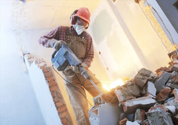 A man with a mask and a hard hat destroys bricks and wall material.