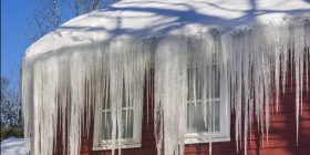 A roof with lots of ice dripping off the eaves.