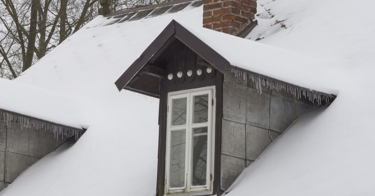 An image of a house with narrow windows and a snow covered roof.
