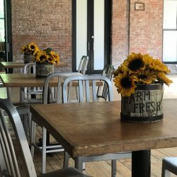 """Image of the indoor gathering space at the Art Farm NYC featuring a table adorned with sunflowers and a basket that says """"Farm Fresh."""""""