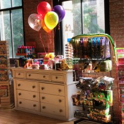 Image of a white dresser, balloons, and other items inside of the Art Farm NYC's toy store.