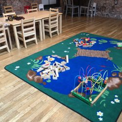 Image of a green and blue rug with blocks and other children's toys inside of the Art Farm NYC's class area.