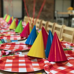 Image of yellow, pink, blue, and green party hats resting on top of plaid plates in the Art Farm NYC's birthday party space.