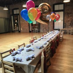 Image of a long party table with balloons for a children's birthday party at the Art Farm NYC.