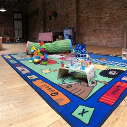 Image of a colorful rug and children's toys inside of the Art Farm NYC's class area.