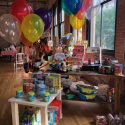 Image of brightly colored children's toys and balloons inside of the Art Farm NYC's toy store.