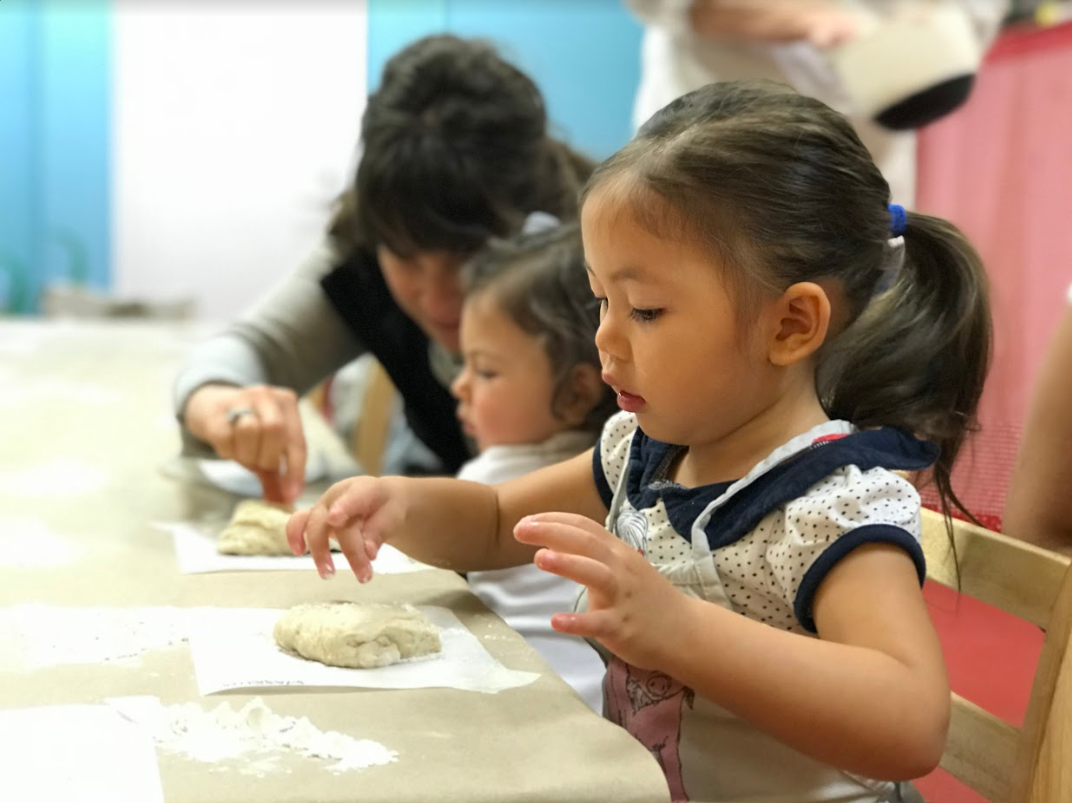 A picture of children sitting at a table and working with flour at The Art Farm NYC.