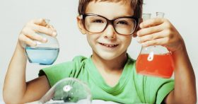 Child in glasses holding two beakers