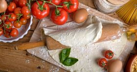 fresh tomatoes and pizza dough rolled with rolling pin