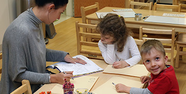 Teacher at Strong Start drawing with two children