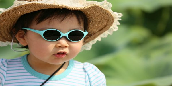 Female toddler in a straw hat and sunglasses