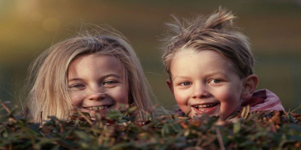 Two young girls peeking up from behind a bush