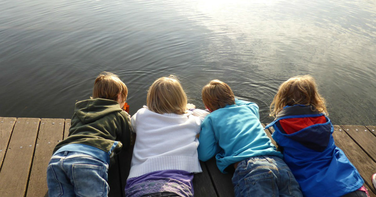 Four kids lying on a pier and watching the water