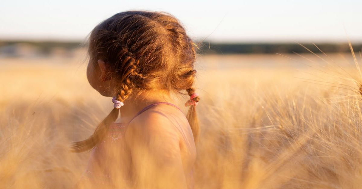 Child in a field looking back at sun